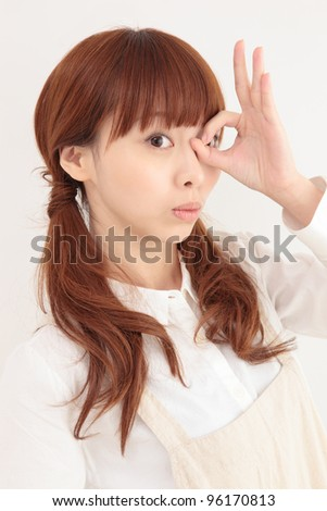 Beautiful young Asian woman wearing a peek apron - stock photo