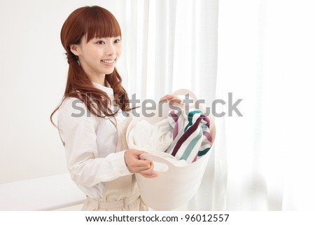 Beautiful young Asian woman with a laundry basket at the window - stock photo