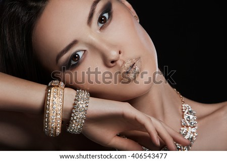Beautiful young asian woman with elegant earrings and necklace - stock photo