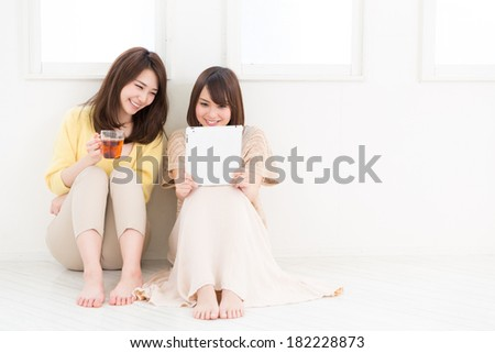 Beautiful young asian women using tablet computer - stock photo