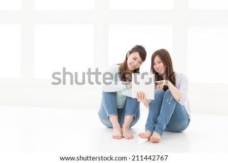Beautiful young asian women using tablet computer - stock photo