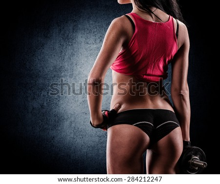 beautiful young athletic couple smiling and doing exercises with dumbbells - stock photo