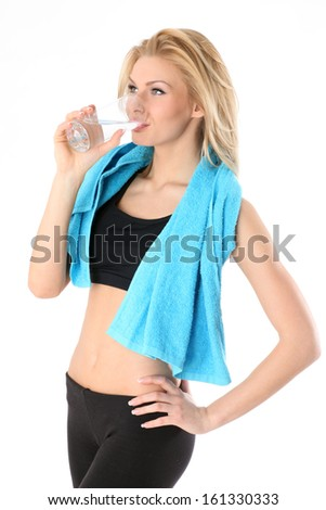 Beautiful, young, athletic girl drinks water after a workout - stock photo