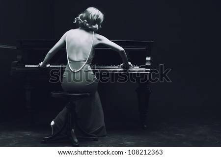 Beautiful young attractive woman in cocktail dress and piano - stock photo