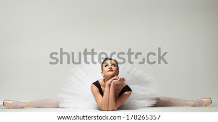 Beautiful young ballerina dancer sitting on a floor - stock photo