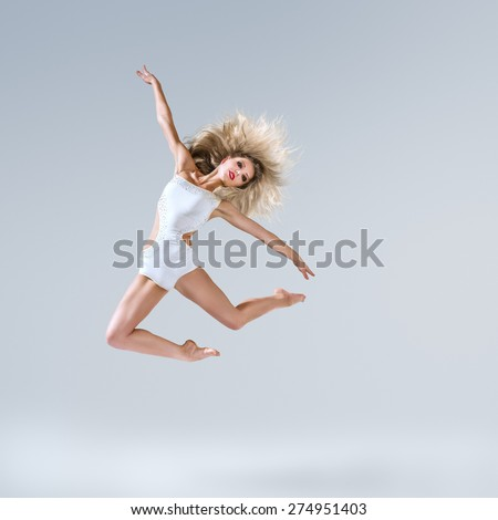 Beautiful young ballet dancer posing in studio - stock photo