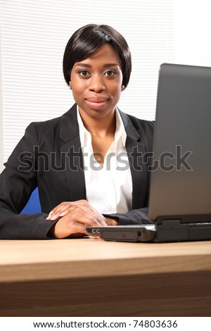 Beautiful young black black business woman working in office sitting to her desk using her laptop, with a serious expression on face. Picture taken from low angle looking upwards. - stock photo