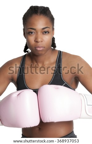 Beautiful young black woman wearing a pair of boxing gloves - stock photo