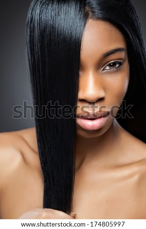 Beautiful young black woman with long straight hair - stock photo
