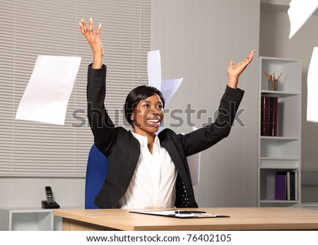 Beautiful young black woman working in office throws a load of papers into the air in happiness. She has a beautiful smile. - stock photo