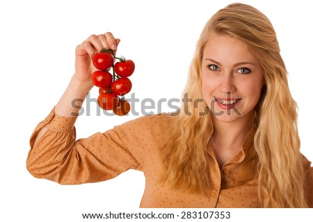 Beautiful young blond caucasian cheerful woman with blue eyes holds red cherry tomatoes isolated over white - stock photo