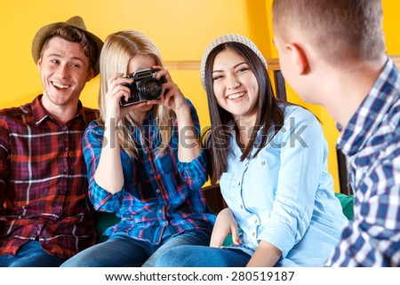 Beautiful young blond girl making a photo of a boy sitting, back using a vintage camera while her friends sitting next to her and watching a process  - stock photo