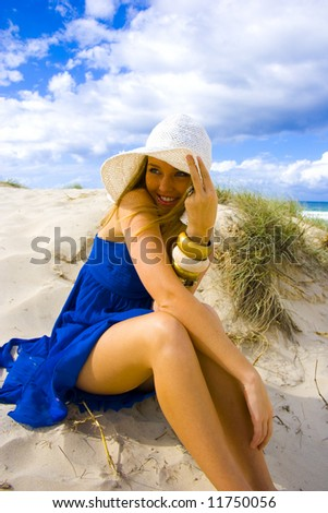 beautiful young blond girl sitting on the beach in a blue dress - stock photo