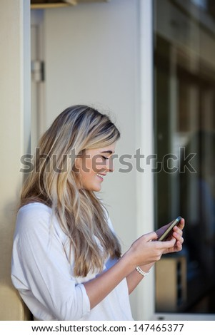 Beautiful young blond girl student sending an sms on a mobile phone while leaning against the exterior wall of a building - stock photo