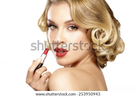 Beautiful young blond model curly hair applying lipstick on white - stock photo