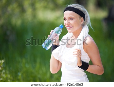 beautiful young blond sporty woman jogging in the park on a warm summer day and drinking water - stock photo