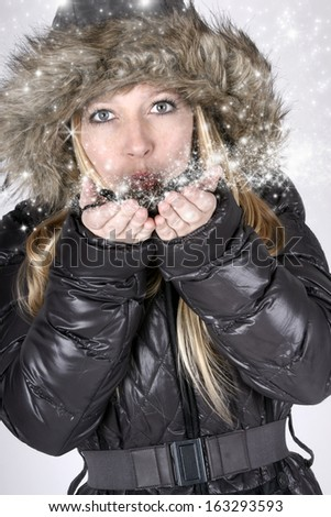Beautiful young blond woman blowing stardust - stock photo