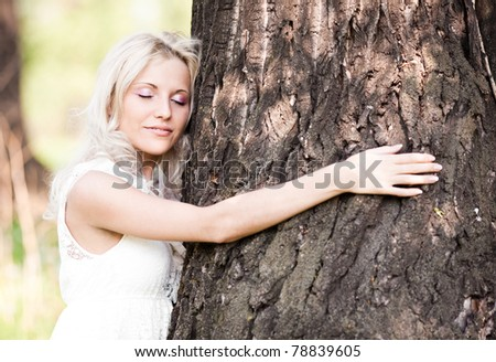 beautiful young blond woman embracing a big tree  on a warm summer day - stock photo