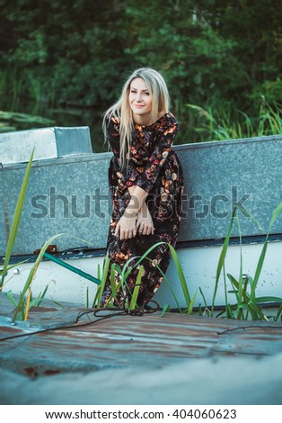 beautiful young blond woman in a long dress with a print walks near the boat pier near the water , a fashionable toning - stock photo