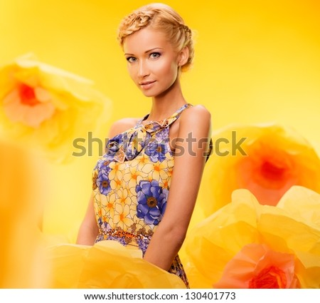 Beautiful young blond woman in colourful dress among big yellow flowers - stock photo