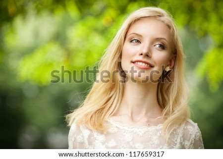 Beautiful young blond woman on abstract green background - stock photo