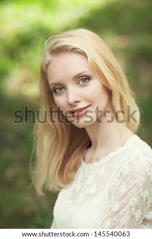Beautiful young blond woman on abstract green background Beautiful young blond woman in a white dress outdoors  - stock photo