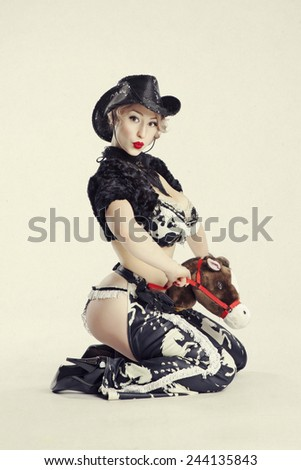 Beautiful young blond woman pin-up in the studio on a white background, dressed as a cowboy. - stock photo
