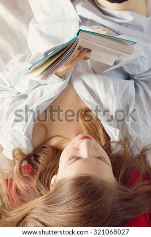 Beautiful young blond woman reading book on the bed at home - stock photo