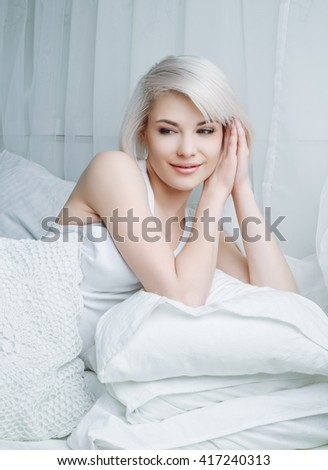 beautiful young blond woman relaxing in bed at home - stock photo