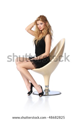 Beautiful young blond woman sitting in white designer chair - stock photo