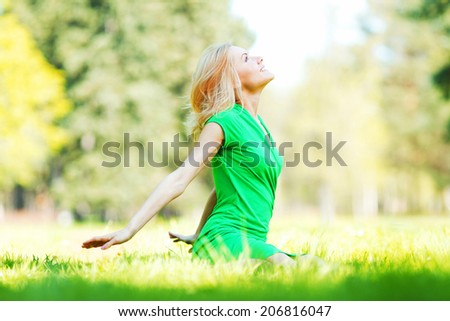 Beautiful young blond woman sitting on grass in park - stock photo