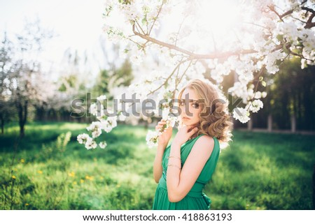 beautiful young blond woman standing beside a blossoming Apple tree on a warm summer day - stock photo