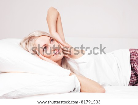 beautiful young blond woman waking up and stretching on the bed at home - stock photo