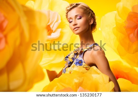 Beautiful young blond woman with closed eyes in colourful dress among big yellow flowers - stock photo