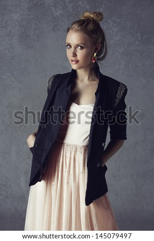 beautiful young blond woman with messy hair in a black blazer and pastel pink dress on grunge studio background - stock photo