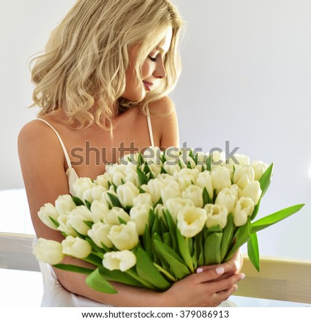 Beautiful young blond woman with tulip bouquet. Spring portrait. At home. Interior. Mother's Day. Springtime - stock photo