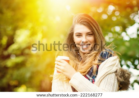Beautiful young blonde Caucasian woman drinking takeaway coffee in park in autumn. Pretty girl with sweater outdoors in fall with coffee cup smiling. - stock photo