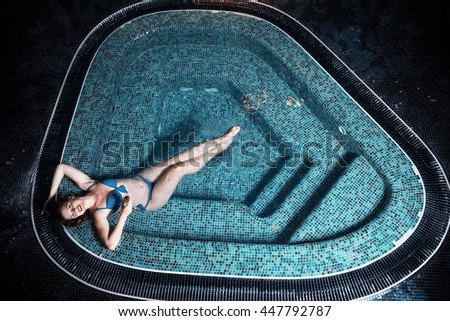 Beautiful young blonde caucasian woman in bikini relaxing in hot pool or jacuzzi at spa center, water treatment and body care concept, top view - stock photo