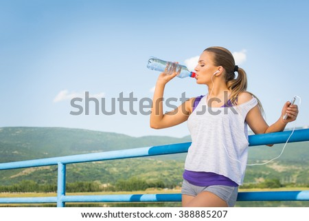 Beautiful young blonde Caucasian woman in sportswear, outdoors on sunny summer day, drinking cold fresh water from the bottle holding smartphone and headphones. Medium retouch, natural light. - stock photo