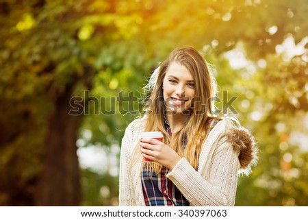 Beautiful young blonde Caucasian woman with takeaway coffee in autumn in park. Happy teenage girl outdoors in fall smiling. Horizontal, medium retouch, vibrant colors, copy space. - stock photo