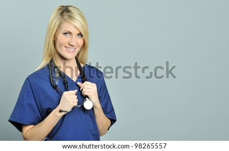 Beautiful young blonde female nurse or physician in blue scrubs holding onto her stethoscope and smiling - stock photo