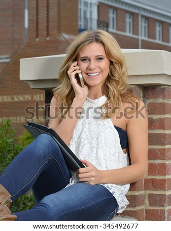 Beautiful young blonde female student on campus - sitting with a tablet computer and on cell phone - stock photo