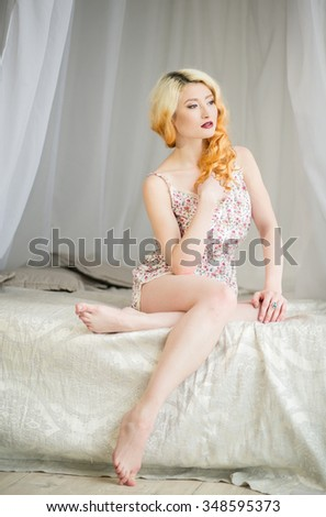 Beautiful young blonde girl in beautiful underwear sitting on a bed in a light bedroom, glamor, sensuality, tenderness, beauty - stock photo