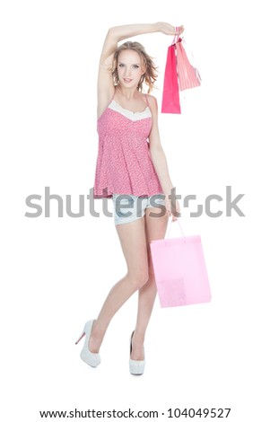 Beautiful young blonde girl in high heels shoes with pink shopping bags over white - stock photo