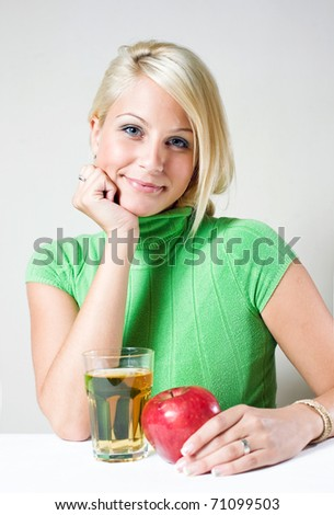 Beautiful young blonde girl with red apple, and a glass of apple juice. - stock photo