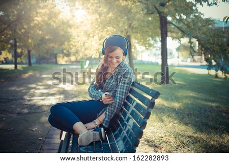 beautiful young blonde hipster woman listening music in the park on the bench - stock photo