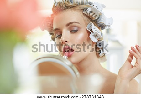Beautiful young blonde lady doing make-up - stock photo