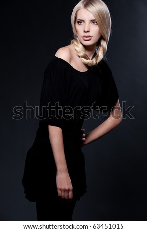 beautiful young blonde posing over dark background - stock photo