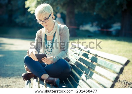beautiful young blonde short hair hipster woman using tablet in the city - stock photo