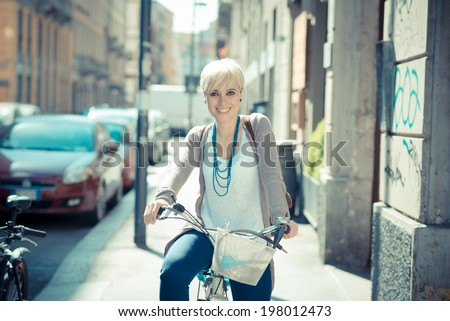 beautiful young blonde short hair hipster woman with bike in the city - stock photo